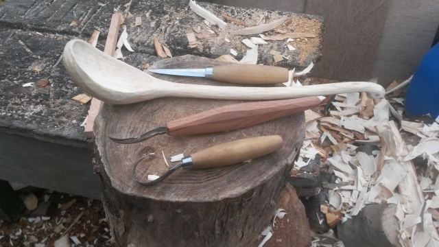 The carving knives next to a ladle I am working on, the straight forward straight carving knife and two hook knives both with different curves to them.